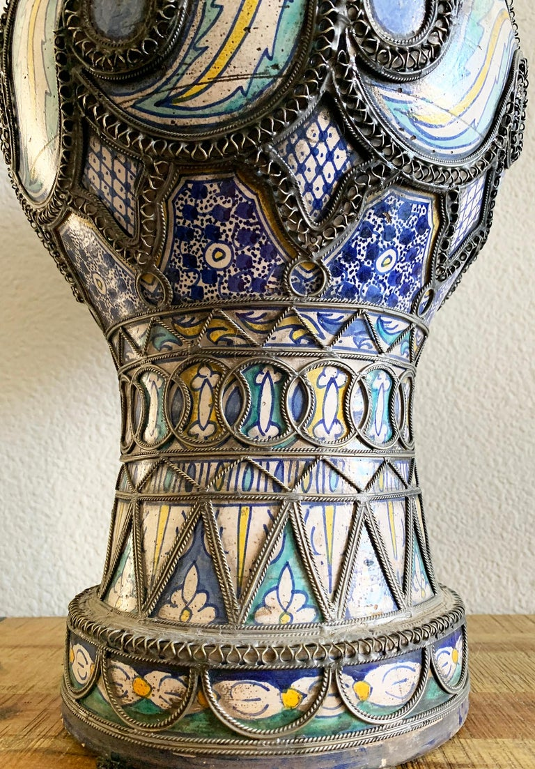An absolutely gorgeous antique Moroccan vase from Fez. This vase features intricate nickel filigree and hand painted blues, teals and yellows. It's in great antique condition with wear and a heavy patina.