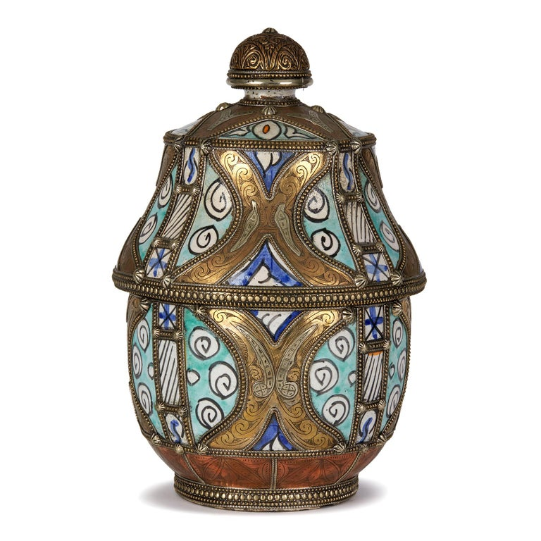 Antique Moroccan 'Jobbana' ceramic lidded butter pot glazed with blue, turquoise and orange with black patterned outlines on a white ground decoration with ornate etched white metal, copper and brass mounts with beaded rims around the edges, the