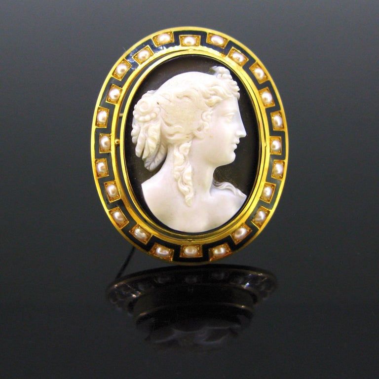 This brooch comes directly from the mid 19th century. It was made in France circa 1860 under the reign of Napoleon III (1852-1870). It features a carved agate cameo depicting a woman looking to the right wearing a rose and some pearls in her hair.
