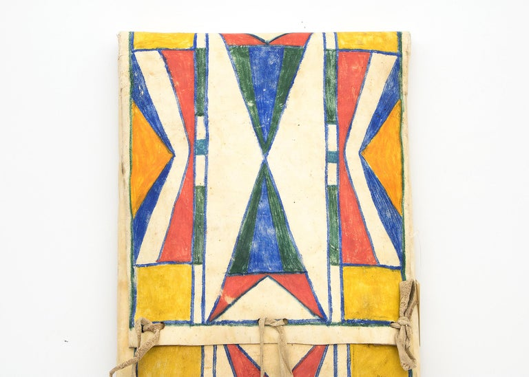 19th century vintage Native American Parfleche container in an envelope form, finely painted circa 1890 in an abstract design with blue, yellow, orange and red by a North American Indian artist of the Plateau Tribe. Makes a stunning wall hanging or