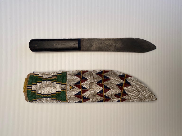 Knife and knife sheath Fully beaded in Classic Cheyenne geometric design on both sides. Beads are sinew sewn on native tanned deer hide. Sheath has rawhide buffalo liner. Sheath includes period knife with steel blade and hardwood handle with three