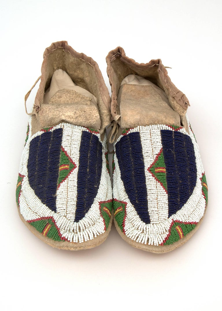 American Indian moccasins, expertly beaded by a member of the Sioux (Plains) tribe. The dark blue elements on the vamps symbolize Buffalo Tracks and the triangular motifs represent teepees. Comprised of glass trade beads on native tanned hide. The