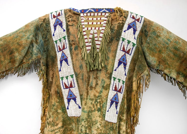 An authentic 19th century Native American Sioux (Plains Indian) beaded war shirt, circa 1880. Native tanned hide beaded with glass trade beads, fringed and painted in green ochre pigment. Dimensions reflect the greatest measurements as displayed on