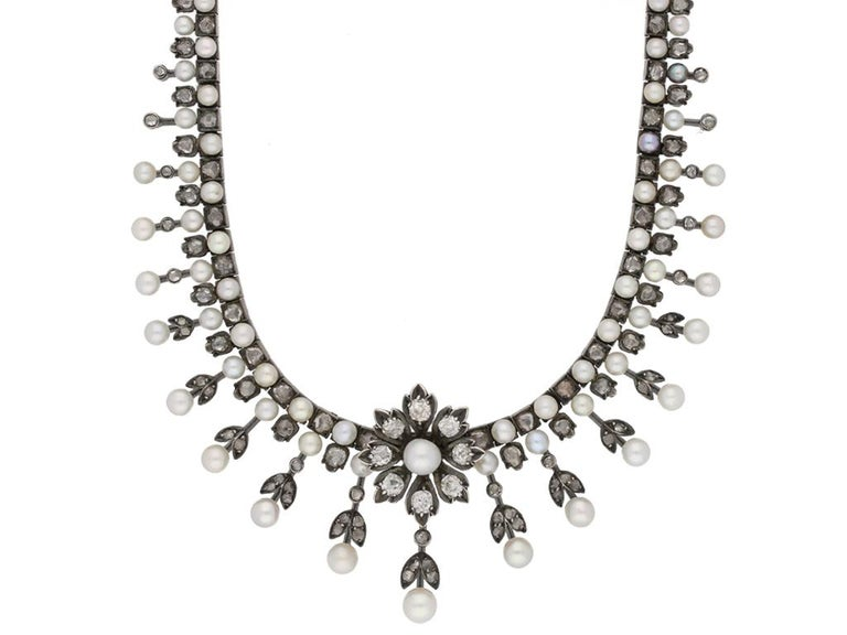 Antique natural pearl and diamond necklace, circa 1880. A gold and silver necklace with one central florette set with a natural round pearl surrounded by eight petals, each set with eight round old cut diamonds in grain settings with an approximate