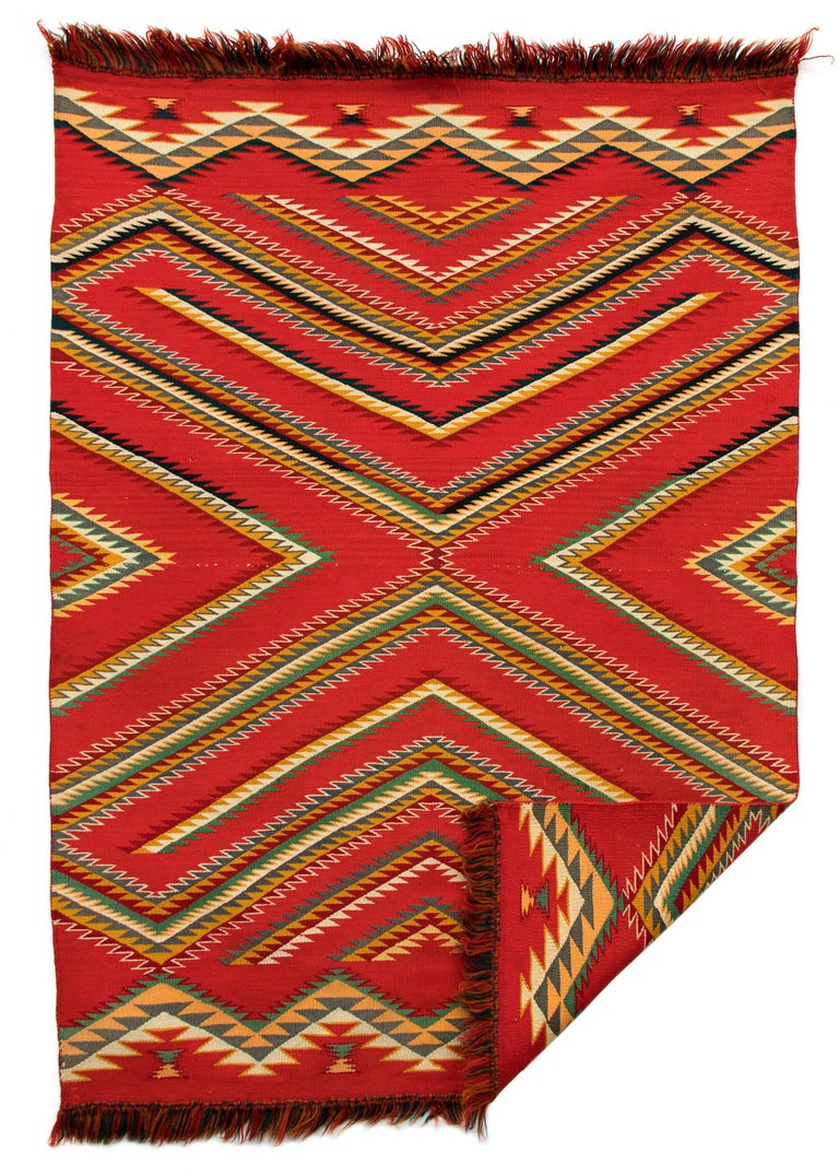 This Germantown blanket is woven of commercial yarns originating from mills in the area of Germantown, Pennsylvania. Navajo weavers appreciated the variety bright colors and even weave found in Germantown wool, creating intricate and vibrant