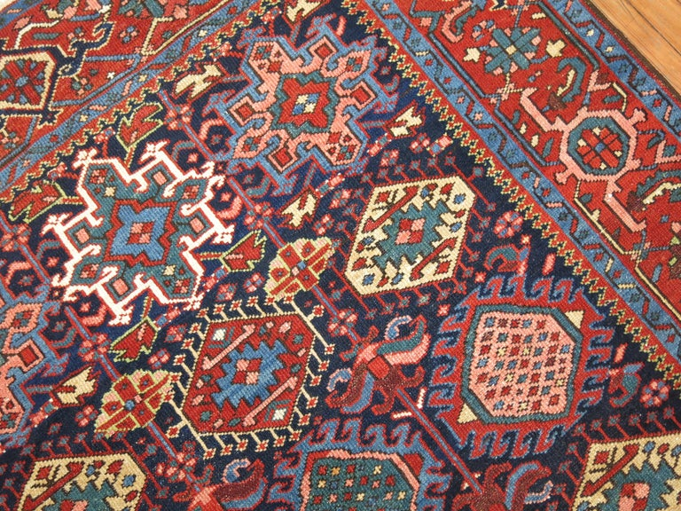 Colorful antique Persian Heriz Karadja rug with an all -over geometric motif on a navy blue ground.