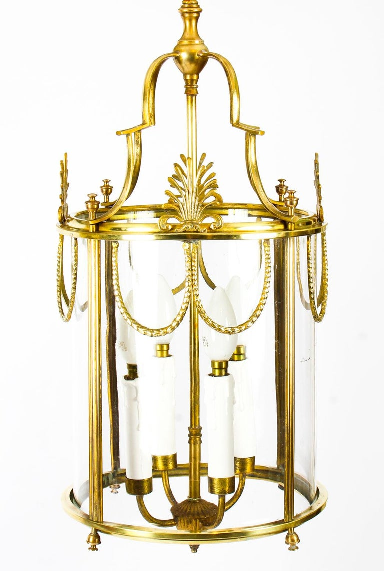 This is an elegant antique neoclassical hanging lantern made of solid brass, circa 1890 in date.  This sophisticated lantern is of circular shape and features a four light pendant which drops off a scrolled canopy.  The frame panels have highly
