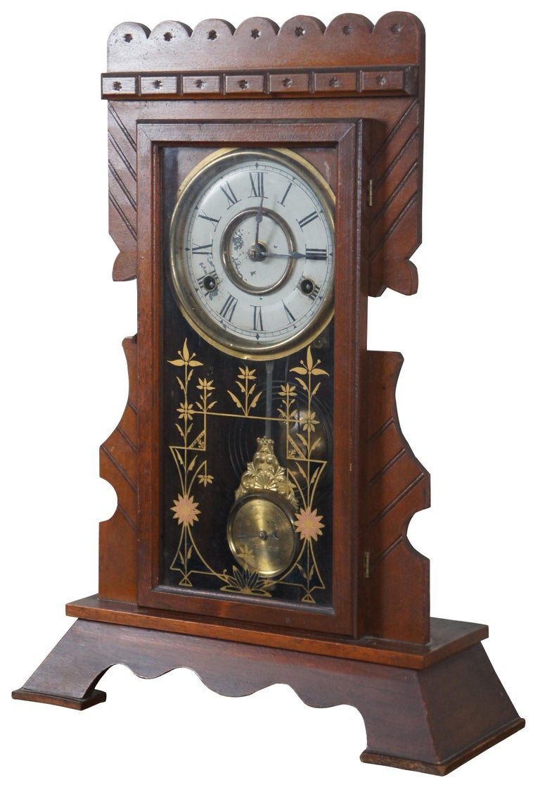 Antique New Haven Clock Company 8 day striking mantel clock model number 511 with carved walnut frame, brass pendulum, painted face and floral painted glass front, Circa 1880s.