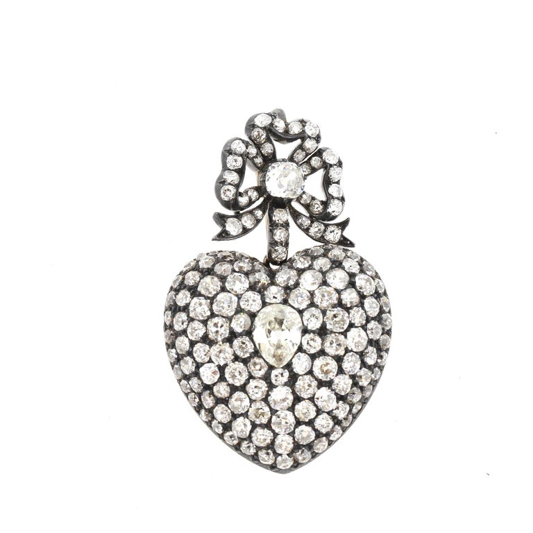 A romantic large scale antique old mine cut diamond heart pendant made around 1890. The heart is suspended from a removable diamond bow and is set with approximately 16 carats of diamonds. The center pear shape diamond weighs approximately 1.30