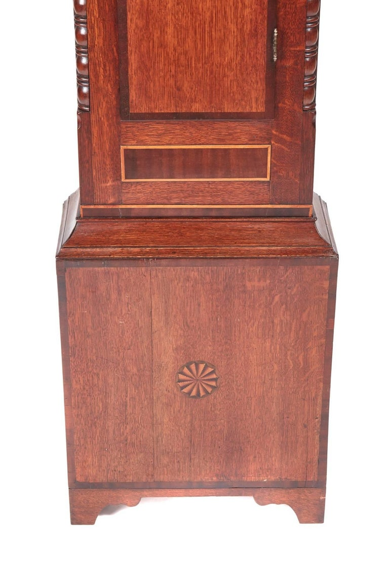 Antique oak and mahogany inlaid 8 day grandfather clock, with a swan-neck pediment lovely decorative arched painted dial with date and seconds dial, 8 day movement striking the hour on a bell, lovely oak and mahogany case with inlaid satinwood
