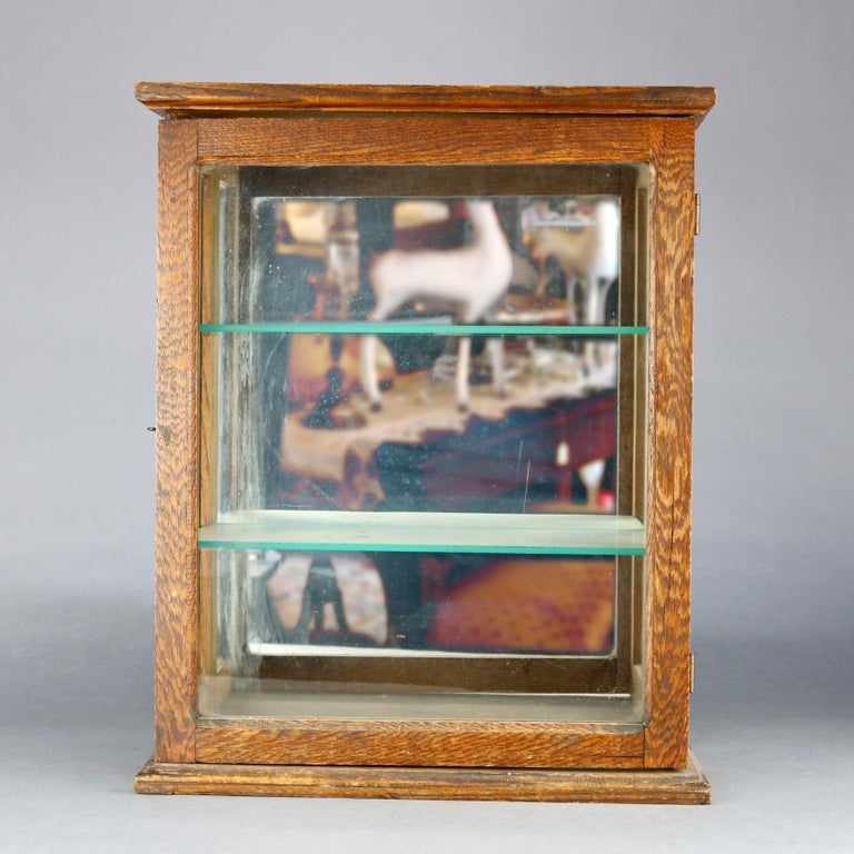 An antique country store display cabinet offers quarter sawn oak construction with glass sides and front door opening to shelved and mirrored interior, circa 1900  Measures: 21.75