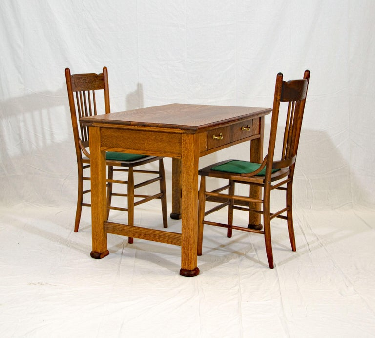 A nice quarter-sawn oak desk or library table and two pressback chairs with the face of the north wind on the back. This table could also be used as a breakfast table in a small kitchen space. The drawer interior height is 3