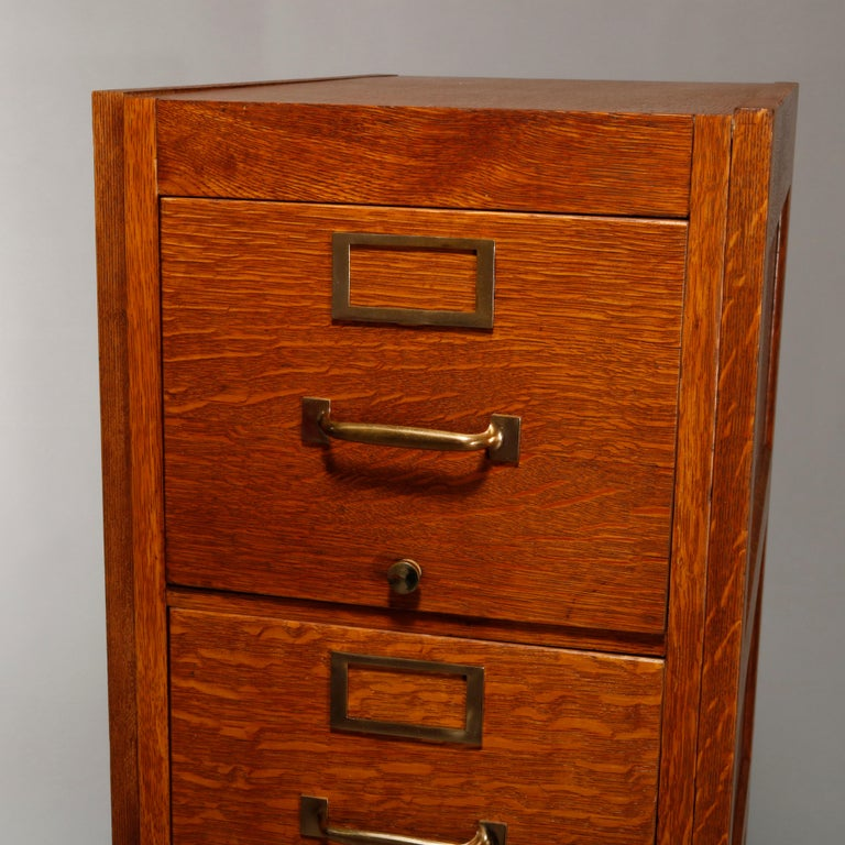An antique file cabinet offers quarter sawn oak construction with paneled sides and five drawers, circa 1900.  Measures: 52.25