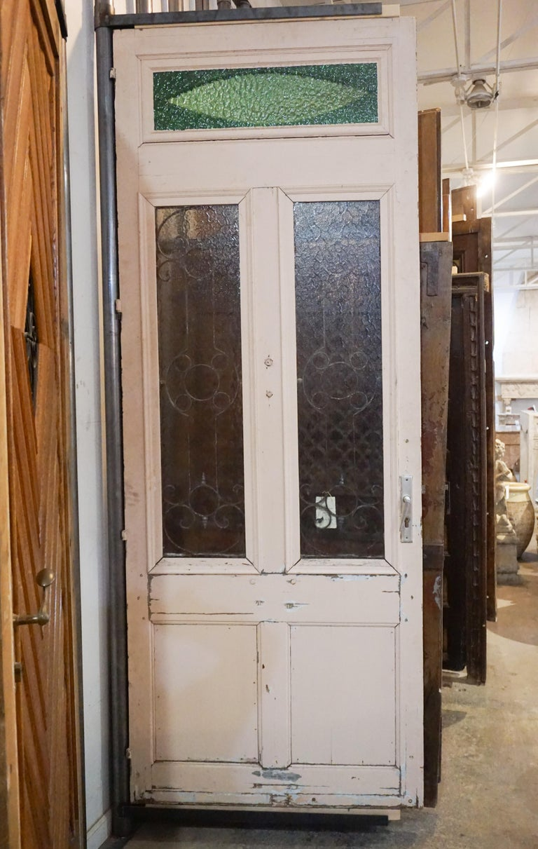 Antique oak, glass and iron work door. Imported from France, circa 1870. This door has tons of character with the hand shaped knocker and green textured window transom.  Measurements: 1.5