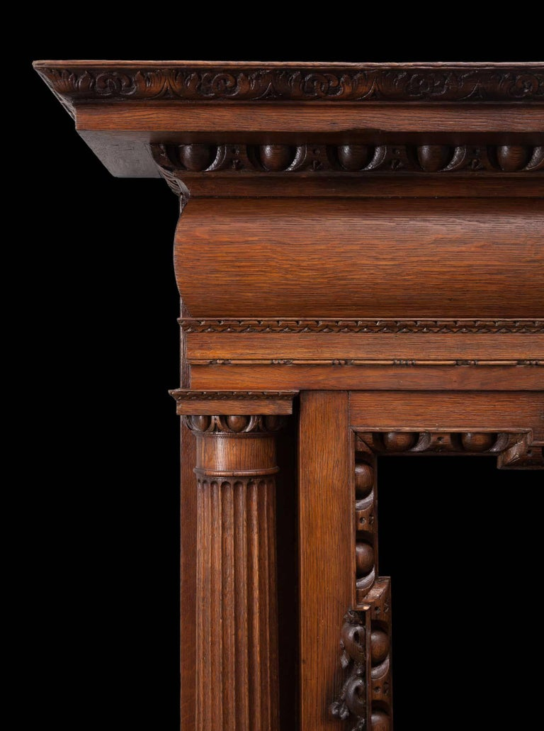 A large antique English carved oak mantelpiece in the Palladian style. With full rounded and fluted Doric columns, egg and dart mouldings and a carved floral centre tablet. Beautifully made during the Victorian period, from a wonderful coloured oak.