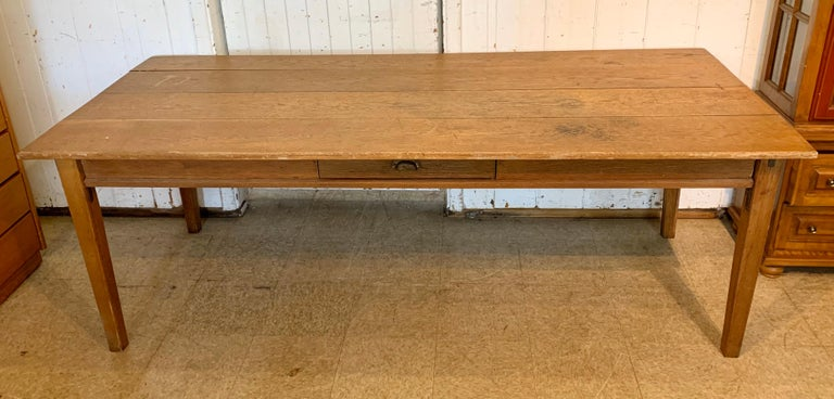 An antique 19th century farmhouse table with a rich and beautiful patina; with a single drawer on one side and two drawers on other side. Four plank top, and tapering legs.
