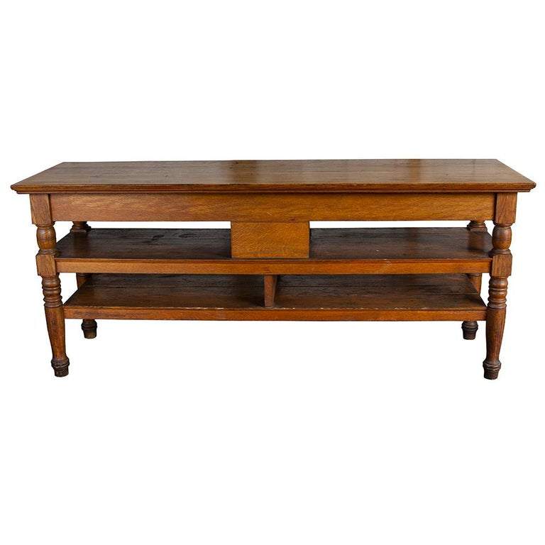 This early 20th century retail display counter has shelving and drawers for plentiful storage, making it an ideal candidate for a kitchen island. Made of solid quarter sawn oak, the chunky turned legs add a touch of easy charm to a handsome and