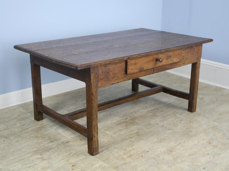 A nicely proportioned oak coffee table with a stretcher base. The wood has good color and patina and the single drawer adds a note of interest.