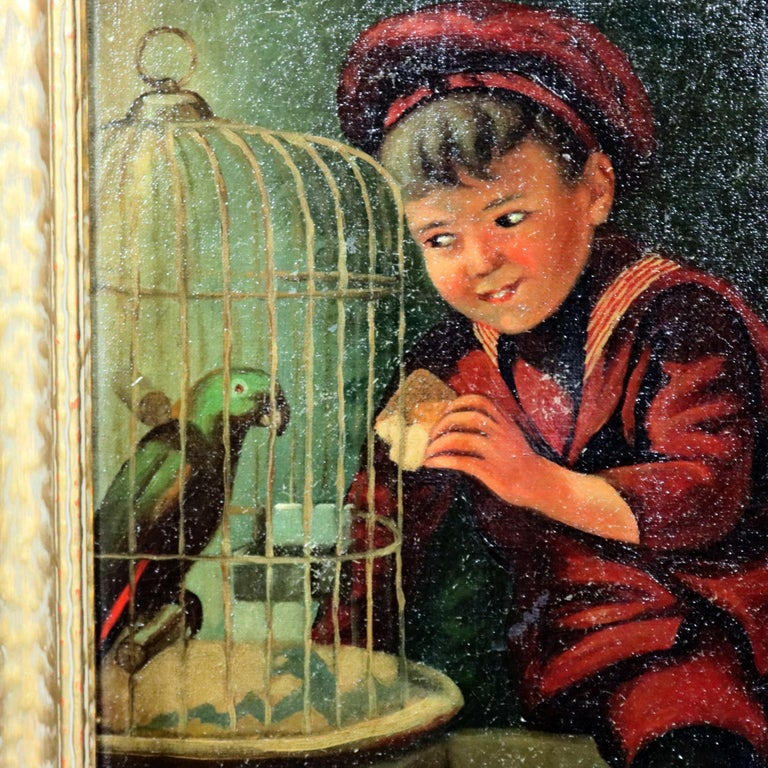 An antique oil on canvas genre painting depicts street urchin boy feeding his caged parrot, artist signed lower right, seated in giltwood frame, circa 1920  Measures: 21.5