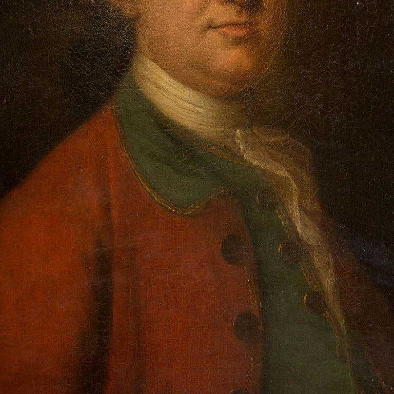 Portrait of an early 19th century gentleman with aristocratic bearing. The white of his collar and lace cuff contrast well against the bright red jacket in the period clothing he is wearing. The canvas is unsigned and mounted in a partial giltwood
