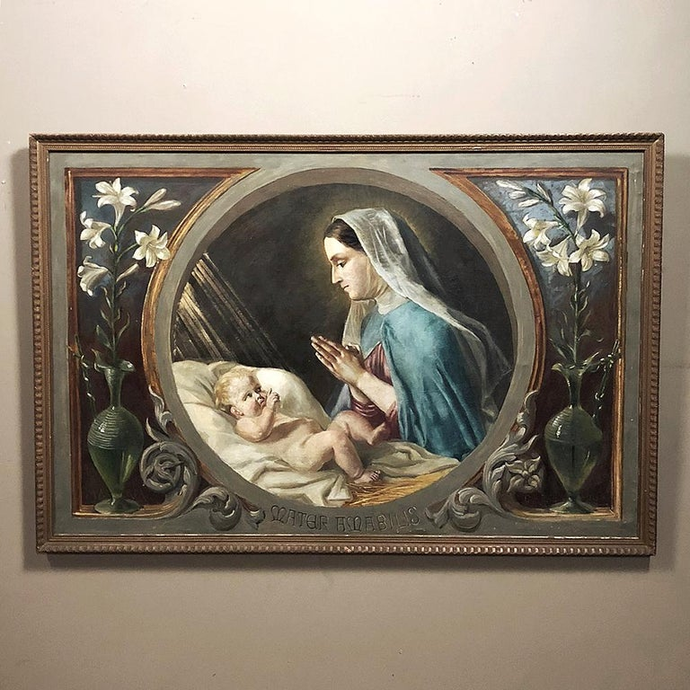 Antique oil painting on canvas of Madonna and child is an idyllic representation of the nativity scene, with the words in Latin inscribed below translating to