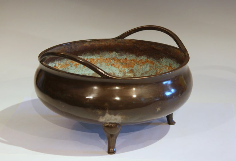 Old and large Chinese bronze censor bowl with great patina, circa 19th-early 20th century. On three feet with pair of undulating handles attached at the rim. 5+ pounds. 11