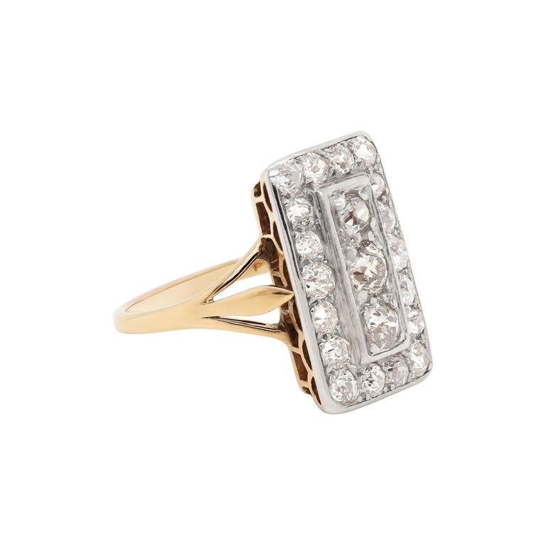 This beautiful rectangular shaped ring features three old mine cut diamonds vertically set in the centre, pavé set within a rectangular border. They are then beautifully surrounded by 18 smaller old mine cut diamonds, also pavé set in open back