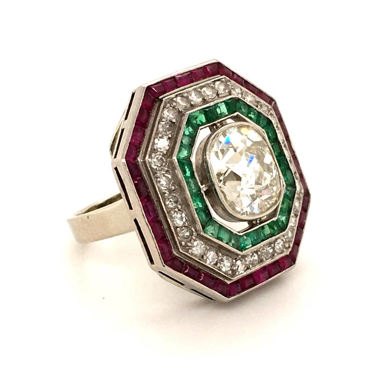 A fantastic tricolor antique diamond ring. The unusual octagonal outline certainly gives it an Art Deco look. Three rows individually channel set with rubies, diamonds and emeralds. Finished in the center with a beautiful old cushion shaped diamond
