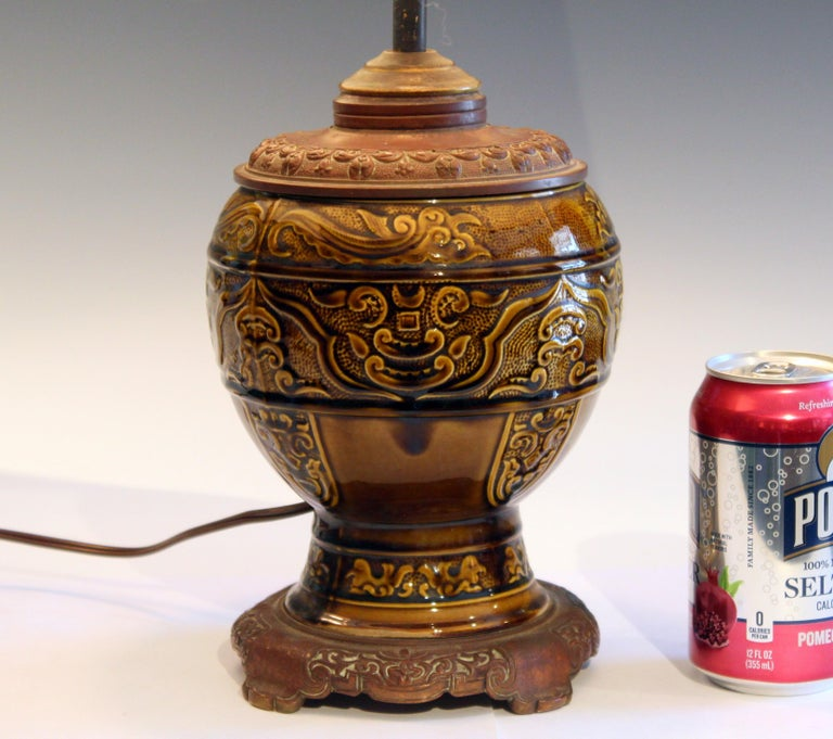 Antique Gien pottery oil lamp converted to electricity, circa late 19th century. Archaic style relief decoration and olive glaze. Nice quality copper base and cap. 20