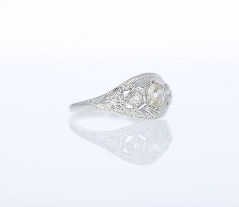 Hand fashioned in 18k white gold this early 20th-century engagement ring is set with a trio of old mine cut diamonds amidst decorative hand engraving and fine millegrain edging.  The three diamonds together weigh approximately 0.45 carat, have an