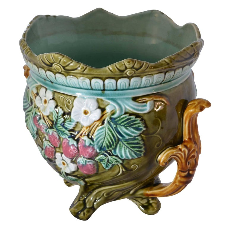 A colorful antique Onnaing French Majolica jardinière is in matching style to the other jardinière. This antique jardinière has a wavy flared rim and a raised floral design on the side with strawberry shaped accents. There is a teal finish inside of