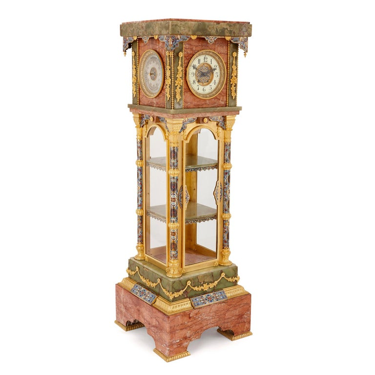 This longcase clock—also known as a vitrine pedestal clock—has been expertly crafted from a combination of the finest materials: green onyx, red marble, golden gilt bronze (ormolu) and colourful cloisonné enamel. In its style, the clock blends