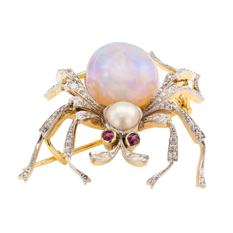 Antique opal diamond ruby pearl gold and platinum spider brooch circa 1900.  DETAILS: Antique gem-set spider brooch mounted in platinum and gold. GEMSTONES: two round rubies, one large oval opal and one pearl. DIAMONDS: fifty-eight round diamonds