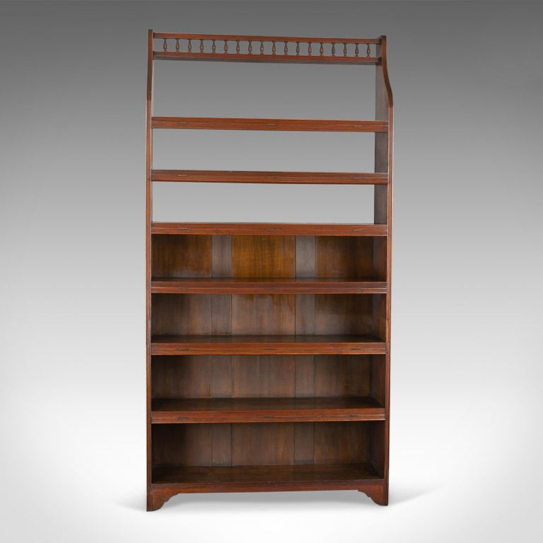 This is an antique open bookcase, tall, English, walnut book shelves. Edwardian, dating to the early 20th century, circa 1910.  Walnut with grain interest in the wax polished finish Six, graduated shelves featuring hinged dust flaps Narrow,
