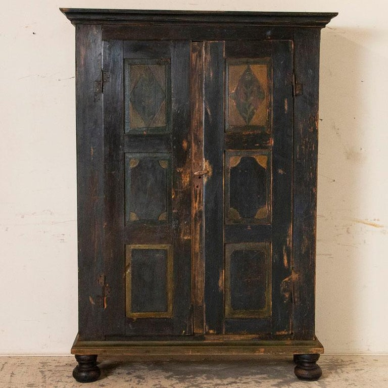 While visually this armoire appears black, it is actually a very dark navy blue that accents this endearing primitive armoire from Lithuania. The heavy pine armoire shows its age in every age-related crack and gouge. It is distressed especially