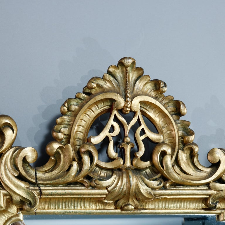 An antique French Louis XIV style wall mirror offer giltwood frame with pierced foliate crest and scroll acanthus elements throughout, c1900.  Measures: 42.5