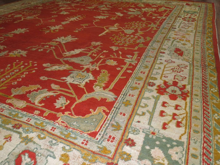 A colorful antique early 20th century Turkish Oushak rug in predominant bright orangy/red field and fresh ivory colored border.   Antique Turkish Oushak rugs have been woven in Western Turkey since the beginning of the Ottoman period. They are still
