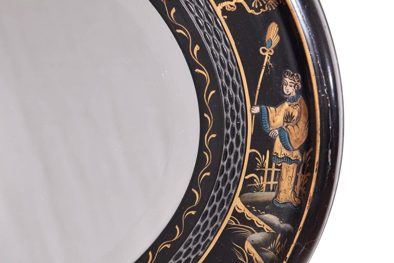 Antique oval chinoiserie lacquered decorated wall mirror with original mirror plate.