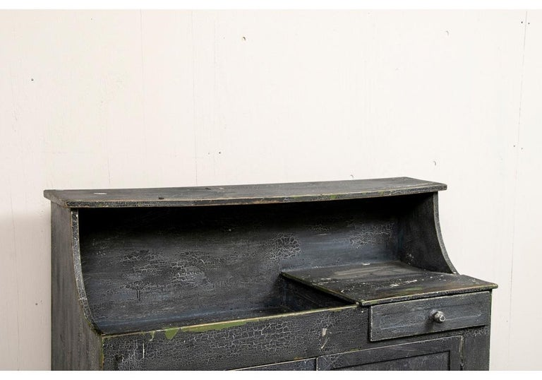 Painted wood in an overall old crackled and worn black paint over a worn green and gilt base paint. The cabinet with sloping sides for the top section. The cabinet right side with a drawer and a dry sink on the left. Below are double doors opening