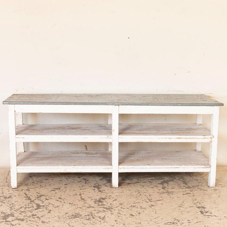 This wonderful old work table can be used multiple ways in a modern home today. This vintage white painted farm work table has the original zinc top and two lower pine wood shelves. The original white paint is greatly distressed adding to the