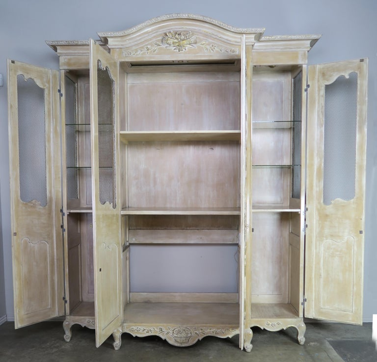 Antique painted Armoire with a white washed finish. The three part armoire has two smaller sections flanking either side of the main frontal portion of the piece. The cabinet stands on cabriole legs with rams head feet. Chicken wire on cabinet door