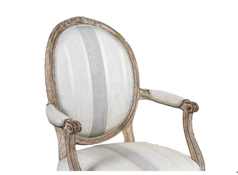 Antique painted Louis XVI style armchair with tapered fluted legs, bow front seat, oval upholstered padded back, striped fabric.