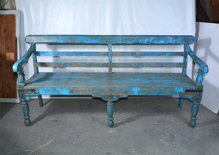 The wonderfully blue-painted Dutch Colonial style solid teak wood bench has slatted back and slightly concave seat for comfort. Metal straps secure all four corners. The front legs and arm supports are turned. Benches like these were used in the