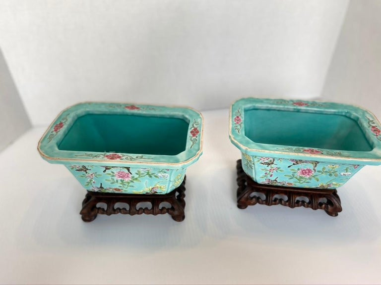 Pair of antique Chinese porcelain jardinières Turquoise ground rectangle shape. Tapering sides. Hand painted floral design on hand made wooden stands that match. 19th century.