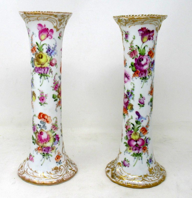 Fine pair of hand painted German hard paste dresden porcelain tall flaring trumpet mantle or desk vases, late nineteenth early twentieth century.  Each with a spiral body rising from a circular spreading gilt base to a flaring rim. The entire