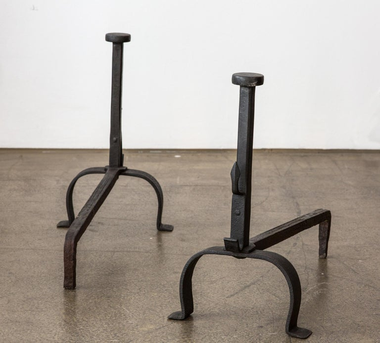 A very decorative pair of antique black wrought iron fireplace andirons. The iron andirons are from Italy and were made at the 19th Century.   The andirons have two feet in front and one single feed at the back. The front feeds are connected with a