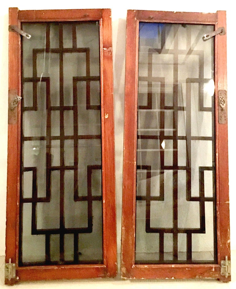 Antique Pair Of Chinese Carved Mahogany Window Panels. Features smoked colored glass and the and fantastic brass hardware. Brass hardware pulls are fantastic cut-out figural owls. Carved geometric lattice wood work is 1