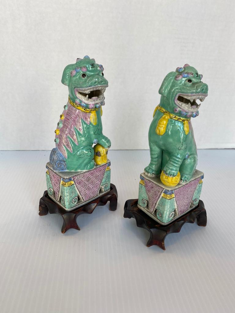 Antique pair of Chinese famille rose porcelain hand painted foo dogs sitting upright, mouths open with hand carved rosewood stands, circa 1890-1910 with CHINA marked to the bottom of all.