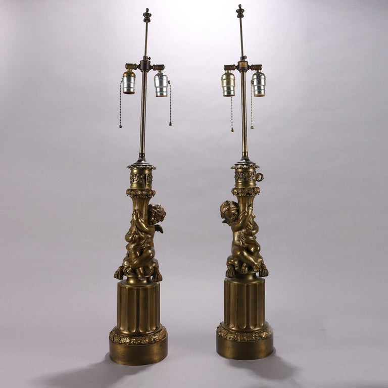 Pair of antique classical bronzed figural lamp bases each feature a cherub seated on tasseled cushion atop Corinthian column base with floral and foliate decoration, each having two independently controlled pull chain sockets, newly rewired and