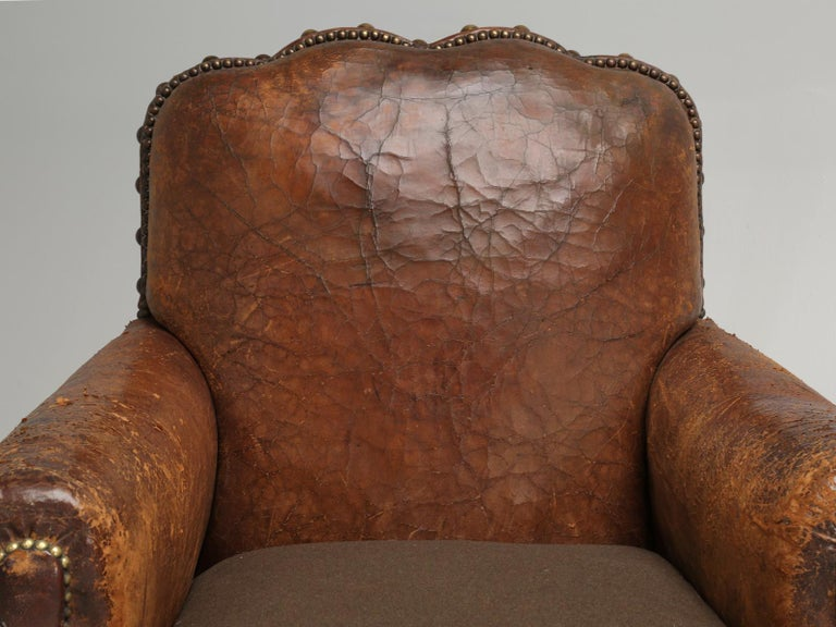 This particular pair of original French leather club chairs are the classic definition of; you can't tell a book by its cover. By that I mean, everything under the skin of that scruffy 90-year old French leather, has been painstakingly restored in a